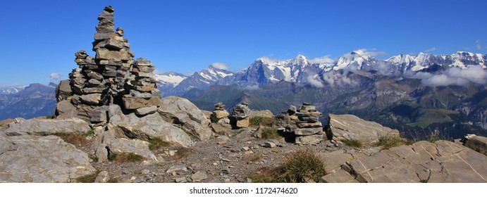 Famous mountains Eiger, Monch and Jungfrau. Stone cairn on top of Mount Niesen.