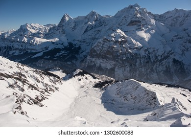 the famous mountains in switzerland eiger monk and jungfrau, below in the picture the mountain village murren which can be reached only with the aerial cableway ore walking.