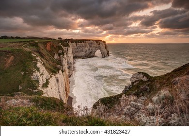 Famous natural arch in Etretat (Normandy, France) at sunset.
