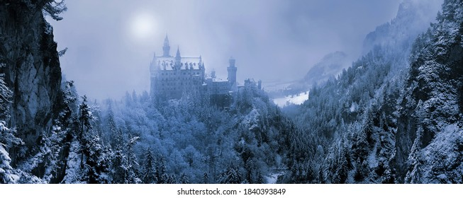 The famous Neuschwanstein Castle in the background of snowy mountains and hills in in the light of the sun through a snowstorm and blizzard. Germany, Europe - Shutterstock ID 1840393849