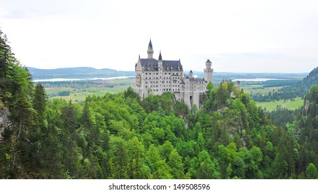 Famous Neuschwanstein Castle overlooking the surrounding valley and meadow, in Schwangau, Germany