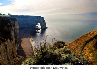 Famous Normandy landscape - panoramic view at Etretat cliffs, pebble beach and sea.