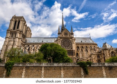 Famous Notre-Dame de Paris cathedral under beautiful blue sky with white clouds.