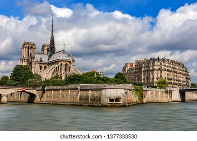 Famous Notre-Dame de Paris cathedral and typical Parisian building under beautiful sky as seen from Seine river.