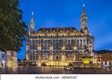 The famous old town hall of Aachen, Germany with night blue sky seen from the market square with the Karls fountain to the right. Taken with a shift lens for straight perspective.