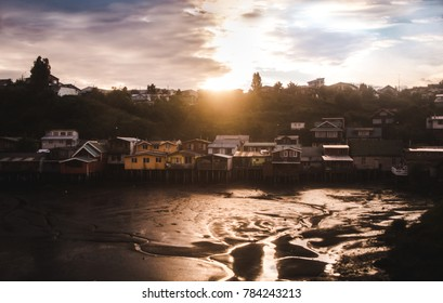 Famous 'palafitos', small wooden houses on stilits on the waterfront during low tide /  sunset in the small town of Castro on Chiloé Island, south Chile