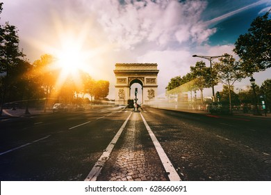 Famous Paris avenue Champs-Elysees and the Triumphal Arch, symbol of the glory on sunny day with sunbeams in sky. Iconic touristic landmark and romantic travel destinations in France. Long exposure