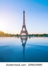 the famous paris eifel tower on a sunny day with some morning sunshine reflects in blue water