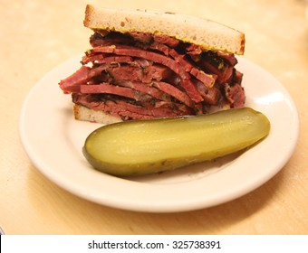 Famous Pastrami on rye sandwich served with pickle in New York Deli