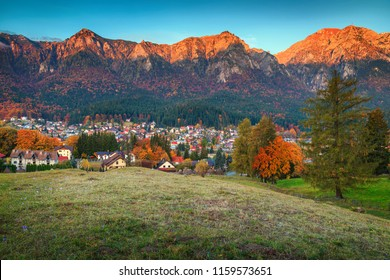 Famous Prahova valley best touristic place, Bucegi mountains in background at sunrise and colorful autumn landscape, Busteni, Transylvania, Romania, Europe