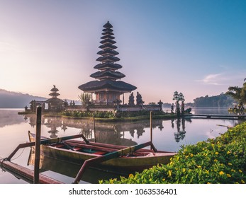 Famous Pura Ulun Danu Bratan temple on Beratan lake in Bali island, Indonesia at foggy sunrise. Iconic image of Bali and southeast asia. Balinese culture and religion concept. Asia Travel Concept.