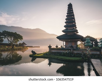 Famous Pura Ulun Danu Bratan temple on Beratan lake in Bali island, Indonesia at foggy sunrise. Iconic image of Bali and southeast asia. Balinese culture and religion concept.