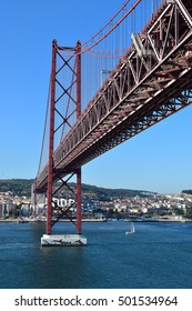 Famous red bridge above the Tejo river in Lisbon, Portugal. Blue sky background.
