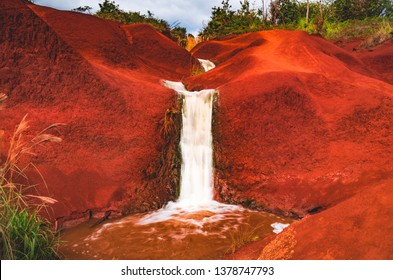 The famous Red Dirt Falls, a cascading waterfall of fresh water over the iron-rich basalt rock in Waimea Canyon State Park, located on the west side of the island of Kauai, Hawaii, United States.
