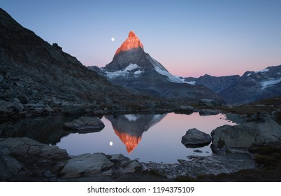 The famous Riffelsee with the moon and the first sunlight shining on the Matterhorn.