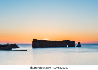 Famous Rocher Perce rock silhouette in Gaspe Peninsula, Quebec, Gaspesie region in Canada with sky and sunrise sun at Saint Lawrence gulf