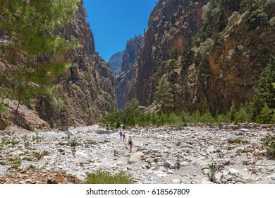 The famous Samaria Gorge in the white mountains on the island of Crete in Greece. Tourists walking along the hiking trail ahead. Dry riverbed.