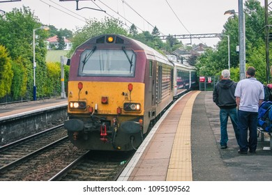Famous scottish caledonian sleeper train is arriving to a platform on a train station on its way to Fort William on a cloudy day.