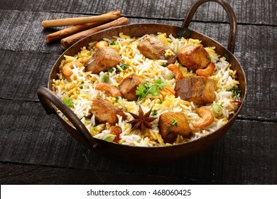 Famous seafood dish-King fish biriyani or pilaf with Indian spices and herbs in a cast-iron pot,