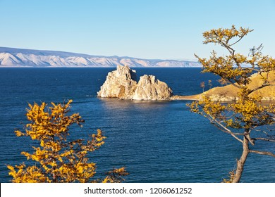 The famous Shamanka Rock is a natural landmark of Olkhon Island on Lake Baikal on an autumn sunny windy afternoon