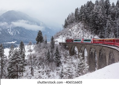 Famous sightseeing train running over viaduct in Switzerland, the Glacier Express in winter