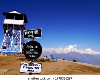 the famous sign and the tower on poonhill with the great himalayan mountains in background.