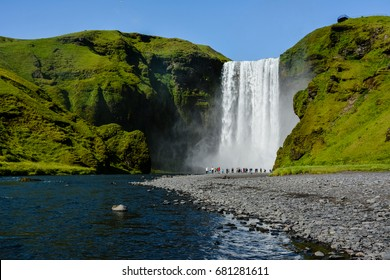 Famous Skogafoss Waterfall, Iceland with colorful tourists visible by water, sunny summer day, blue sky