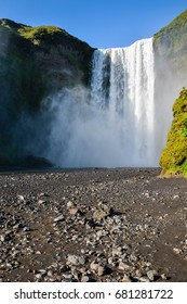 Famous Skogafoss waterfall in Iceland with rainbow on sunny summer day, nobody in photo.