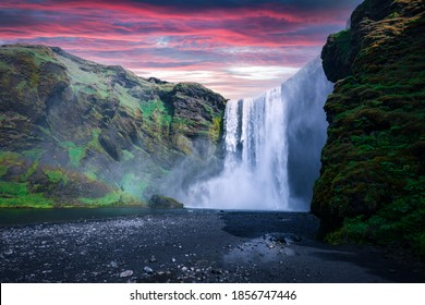 Famous Skogafoss waterfall on Skoga river in sunset time. Iceland, Europe. Great purple sky glowing on background. Landscape photography