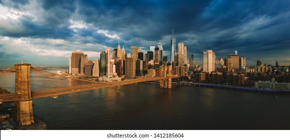 Famous Skyline of downtown New York and Manhattan wiith Brooklin Bridge at the early morning sun light during stormy clouds and sun, New York City, USA