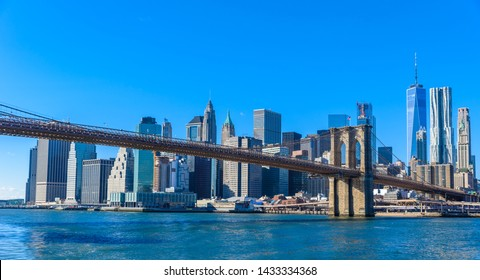 Famous Skyline of downtown New York City, Brooklyn Bridge and Manhattan with skyscrapers illuminated over East River panorama. New York, USA