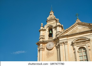 The famous St Paul's Cathedral (Mdina Cathedral). View ot church tower with the bell and the turret clock on a sunny day with blue sky. A cross is on the roof. Vacation on the island of Malta.