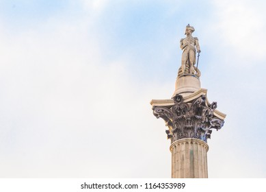 Famous statue of Admiral Nelson on Trafalgar Square in London, UK, on blue clear sky.