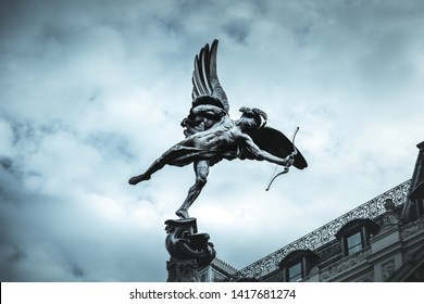 Famous statue of Eros, Amor, Cupid at Piccadilly Circus in London, UK, on blue clear sky and dramatic background