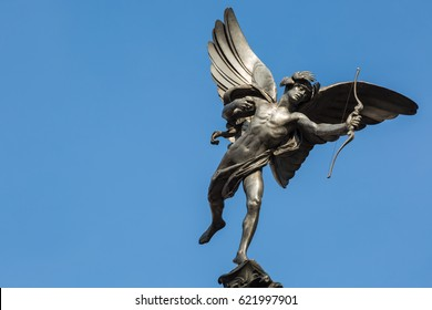 Famous statue of Eros, Amor, Cupid at Piccadilly Circus in London, UK, on blue clear sky