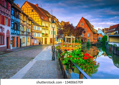 Famous summer travel destination, stunning colorful traditional houses and paved touristic street decorated with flowers at sunrise, Colmar, France, Europe