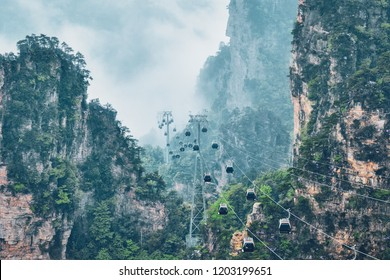 Famous tourist attraction of China - Zhangjiajie stone pillars cliff mountains in fog clouds with cable railway car lift at Wulingyuan, Hunan, China. With camera pan