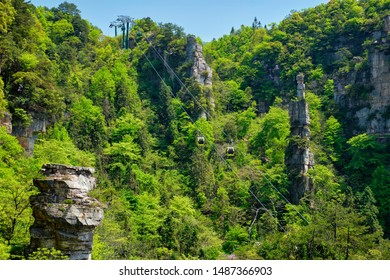 Famous tourist attraction of China - Zhangjiajie stone pillars cliff mountains with cable railway car lift at Wulingyuan, Hunan, China. With camera pan