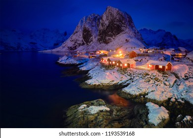 Famous tourist attraction Hamnoy fishing village on Lofoten Islands, Norway with red rorbu houses in winter snow illuminated in the evening