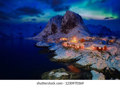 Famous tourist attraction Hamnoy fishing village on Lofoten Islands, Norway with red rorbu houses in winter snow illuminated in the evening with Aurora Borealis