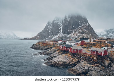 Famous tourist attraction Hamnoy fishing village on Lofoten Islands, Norway with red rorbu houses. With falling snow in winter