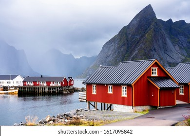 Famous tourist attraction Hamnoy fishing village on Lofoten Islands, Norway with red and yellow rorbu houses. Calm, blurred water