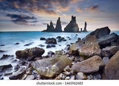 Famous tourist landscape with basalt rock formations Troll toes (Trolls fingers) on black beach. Ocean waves flow around stones. Reynisdrangar, Vik, Iceland, Atlantic Ocean, Europe. Travel postcard.