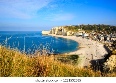 Famous tourist town Etretat in Normandy, France. Landscape view from the cliff overlooking small town.