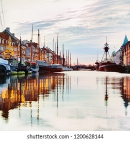 Famous touristic place in Copenhagen - nyhavn early morning reflection of boats at harbor.
