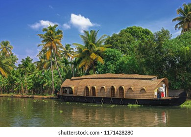 Famous traditional houseboats in back waters with palm trees and greenery in background, Alappuzha,Alleppy,Kerala South India,Asia