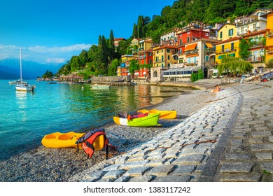 Famous travel and tourism location with colorful buildings. Summer holiday resort with colorful canoes, kayaks and boats, Varenna, lake Como, Italy, Europe. Vacation and relaxation concept