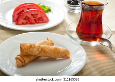 Famous Turkish rolls called sigara boregi, served with tomatoes, black olives and tea.