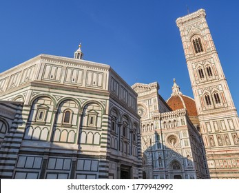 Famous UNESCO Complex in Piazza del Duomo of Florence. Baptistery of Saint John next to the Florence Cathedral of Saint Mary of the Flower, with red-tiled roof or cupola, and Giotto bell tower.