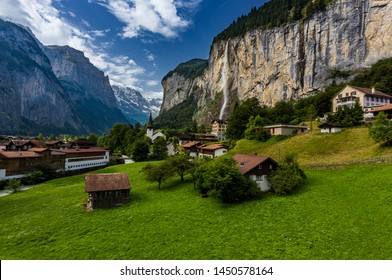 Famous view of Lauterbrunnen town in Swiss Alps valley with gorgeous Staubbach waterfalls in the backgroud, Switzerland.
